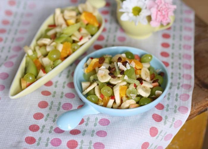 Banan, äpple, vindruva och andra frukter i skålar på rosa och vit duk.