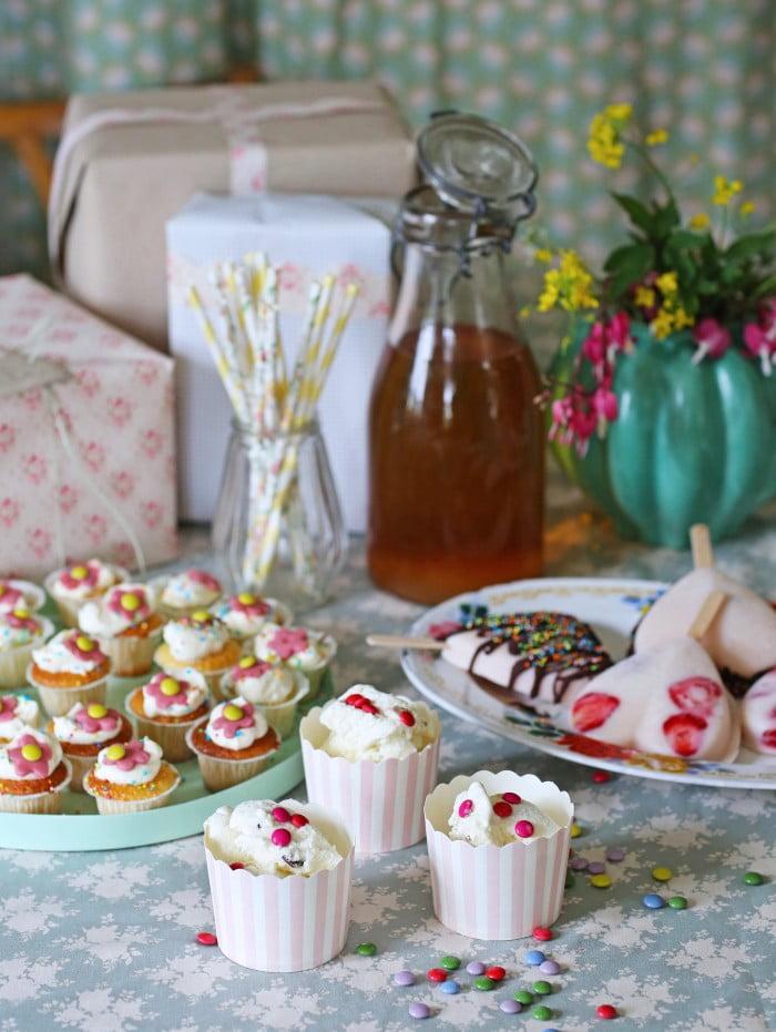 Uppdukat festbord med glass och små muffins i pasteller.