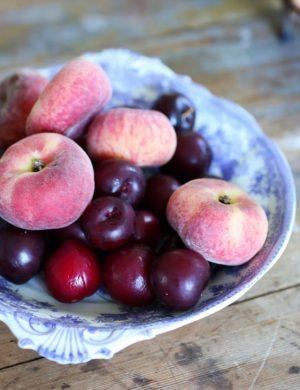 Persikor och plommon i blåblommigt fat.