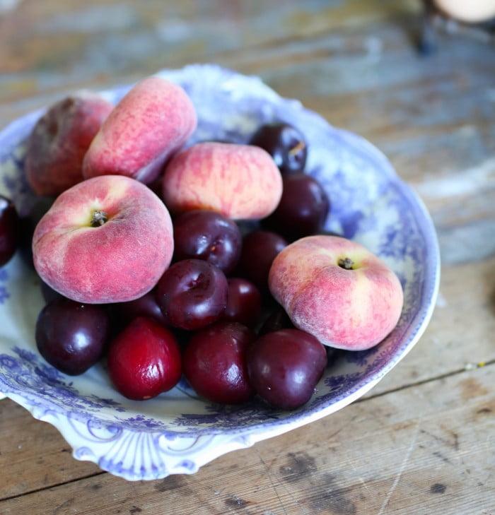 Färska persiokor och plommon i blåvitt porslin.