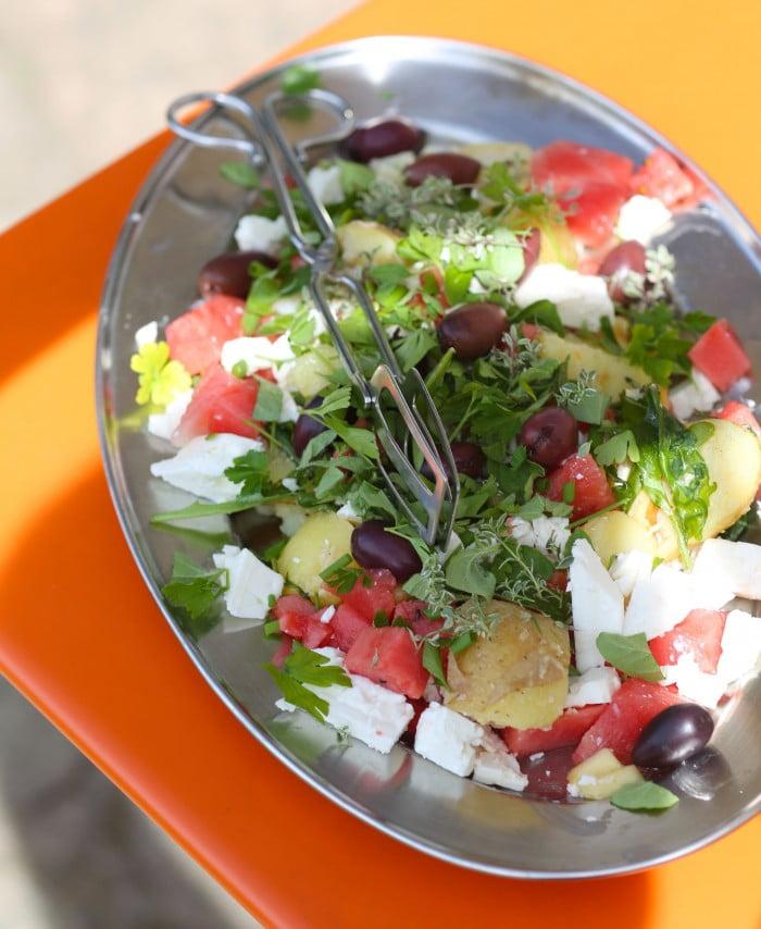 Sallad med oliver och feta på silverfat.