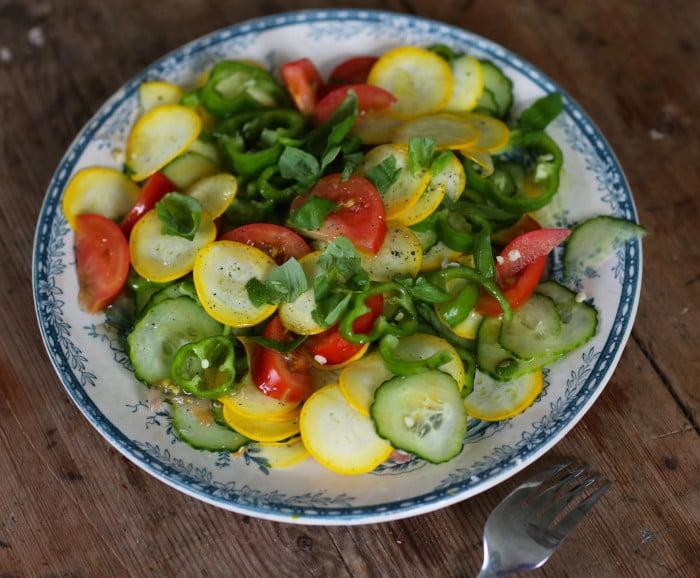 Gul skivad squash, gurka, paprika och röda tomater i en sallad.