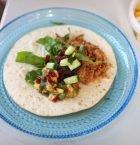 Ljus blå glastallrik med tortilla och ovanpå grönsaker och köttgryta i bitar.