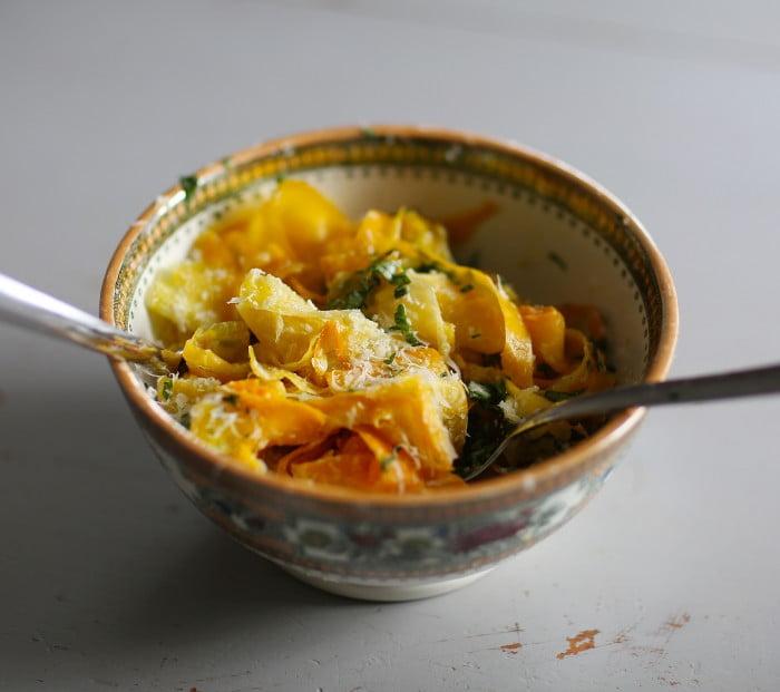 En hyvlad gyllene squash som fått smak av citrus i en porslinsskål.