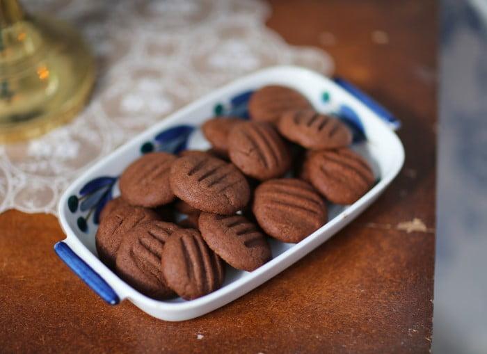 Bruna runda småkakor i blått kakfat.