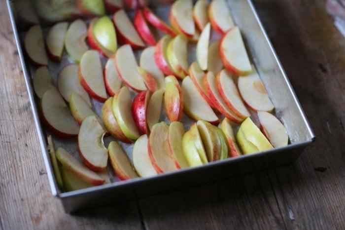 Äpplen skivade både tunt och lite grövre i botten av kakform.
