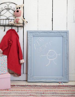 """Liten ljus tavelram målad i samma färg till en griffeltavla, innanför ramen står det skrivet med skolkrita """"Bertil"""" och bredvid är en glad gubbe."""
