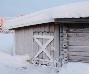 Vit frostig timmerlada med snö på och runtomkring i vinterlandskap.