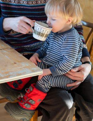 Sonen Folke i knä på pappa samtidigt som han blåser och doftar ner i kaffekopp.