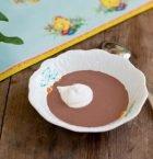 Liten porslinstallrik med chokladsoppa och en klick grädde på bord med påskduk.