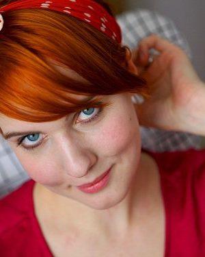 Clara i morotsrätt hår uppsatt med hårband, tittar in i kameran och ler.