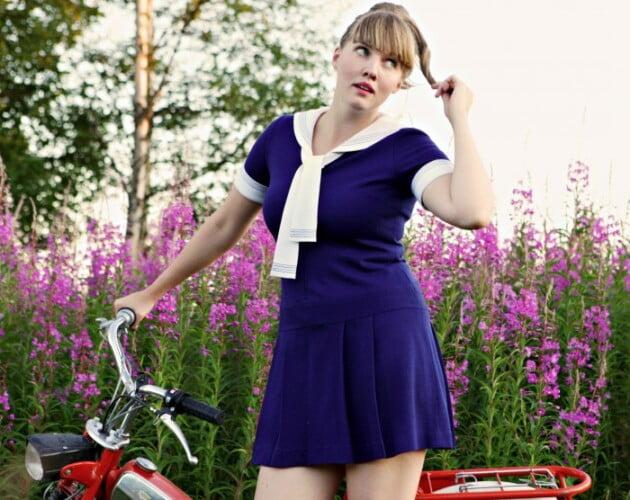 Sommarbild med Clara i blå kort sjömansklänning och hästsvans, står vid röd gammal moped framför äng av rallarrosor.