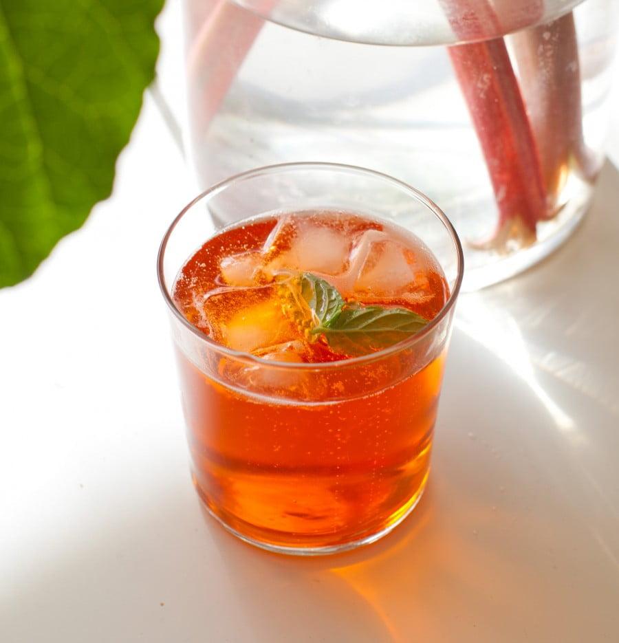 Rödorange alkoholfri drink i genomskinligt glas på sommarbord.