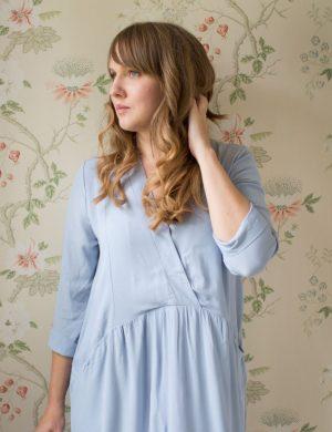 Clara klädd i mild ljusblå klänning med v-ringning.