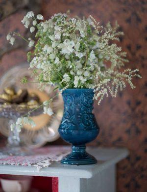 Ljusa sommarblommor i blå vas på vitt bord och ett fat med kakor.