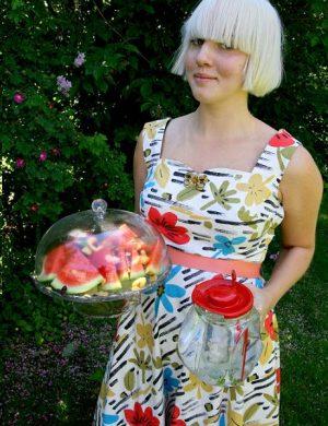 Clara i isblond page håller ett fat med skuren melon och bär själv en sommarklänning i många glada färger.