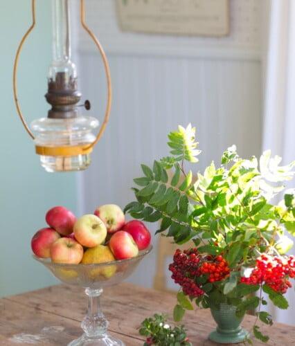 Köksbord i höstsol med rönnbärsbukett och skål med äpplen i gult och rött.