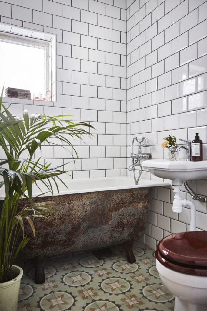 Claras badrum med vitt kakel och gammalt badkar.