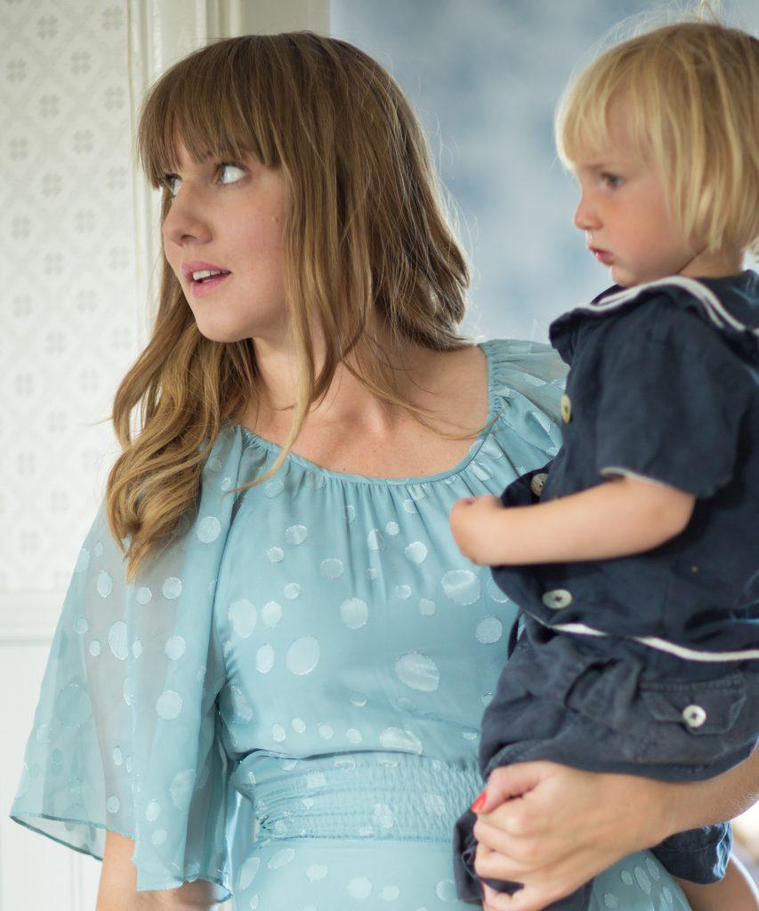 Clara i ljusblå känning med sonen Folke på armen.