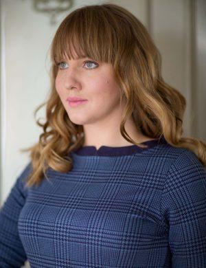 Clara i blå fodralklänning och lugg.