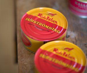 Rödgula plåtburkar med surströmming står oöppnade på träbord.