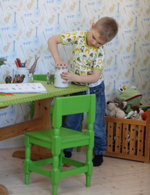 Pojke leker i barnrum intill skrivbord med grönmålad stol.