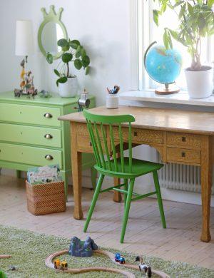 Arbetsrum med äldre möbler och grönmålad pinnstol i mitten. I fönstret står en jordglob.