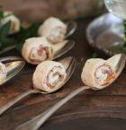 Laxsnittar skurna i bitar och lagda i stora silverskedar på matbord.