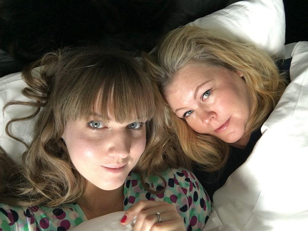 Clara och Erica nedbäddade i en hotellsäng med vita lakan.