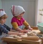 Barn som bakar på bakbord i kök med hucklen av kökshandukar på huvudena.