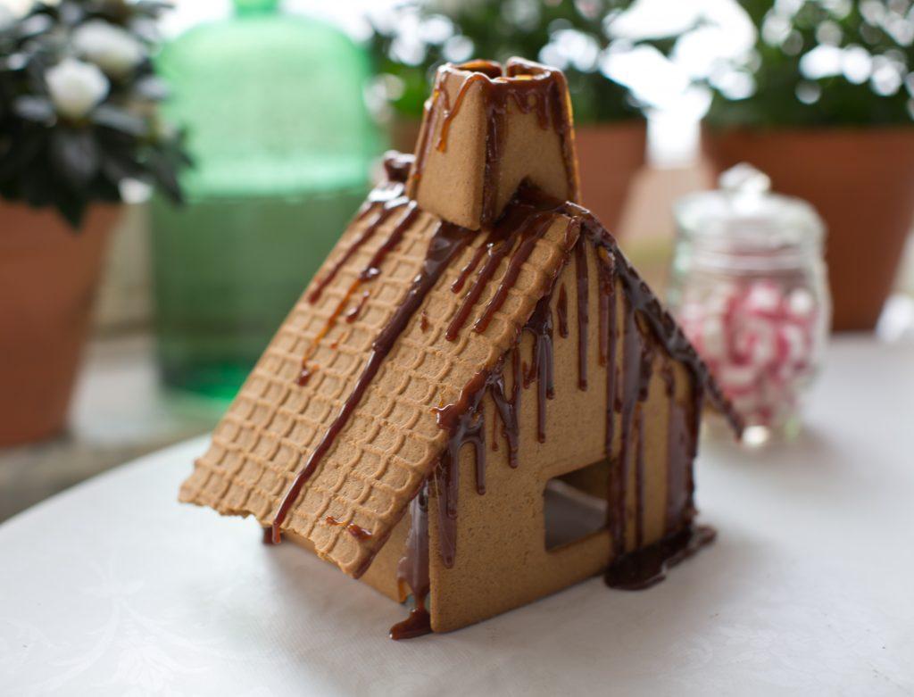 Brunt trasigt pepparkakshus som lappats ihop av smält socker.