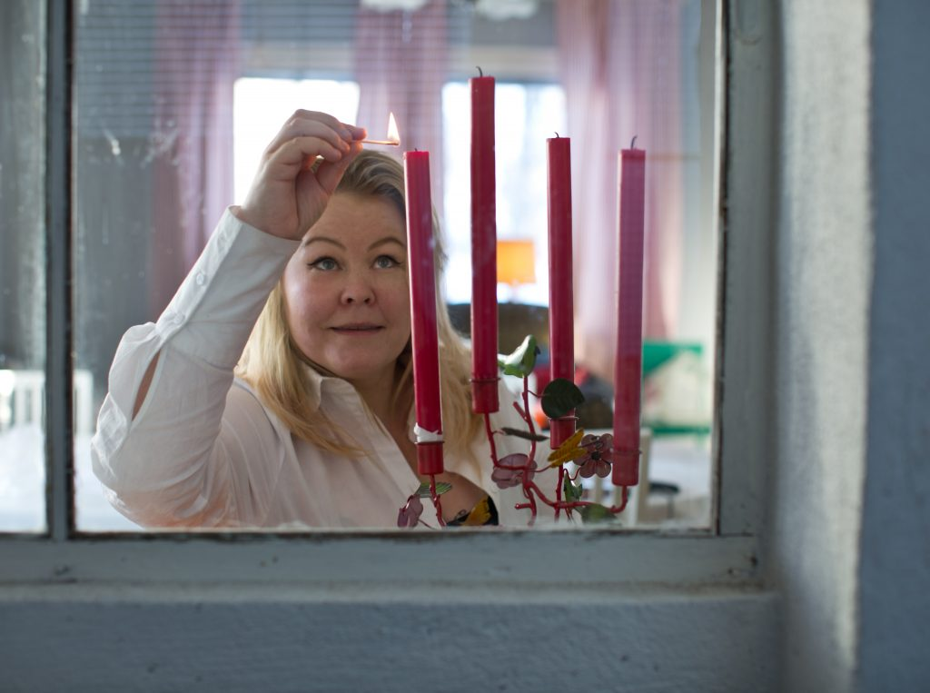 Erica tänder röda ljus i adventsklätt vardagsrum vid inspelning av En Underbar Pod.