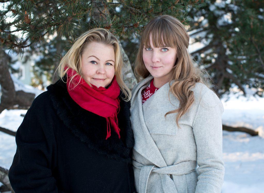 Clara och Erica klädda i vinterkläder framför tallris utomhus, fotat för En Underbar Pod.
