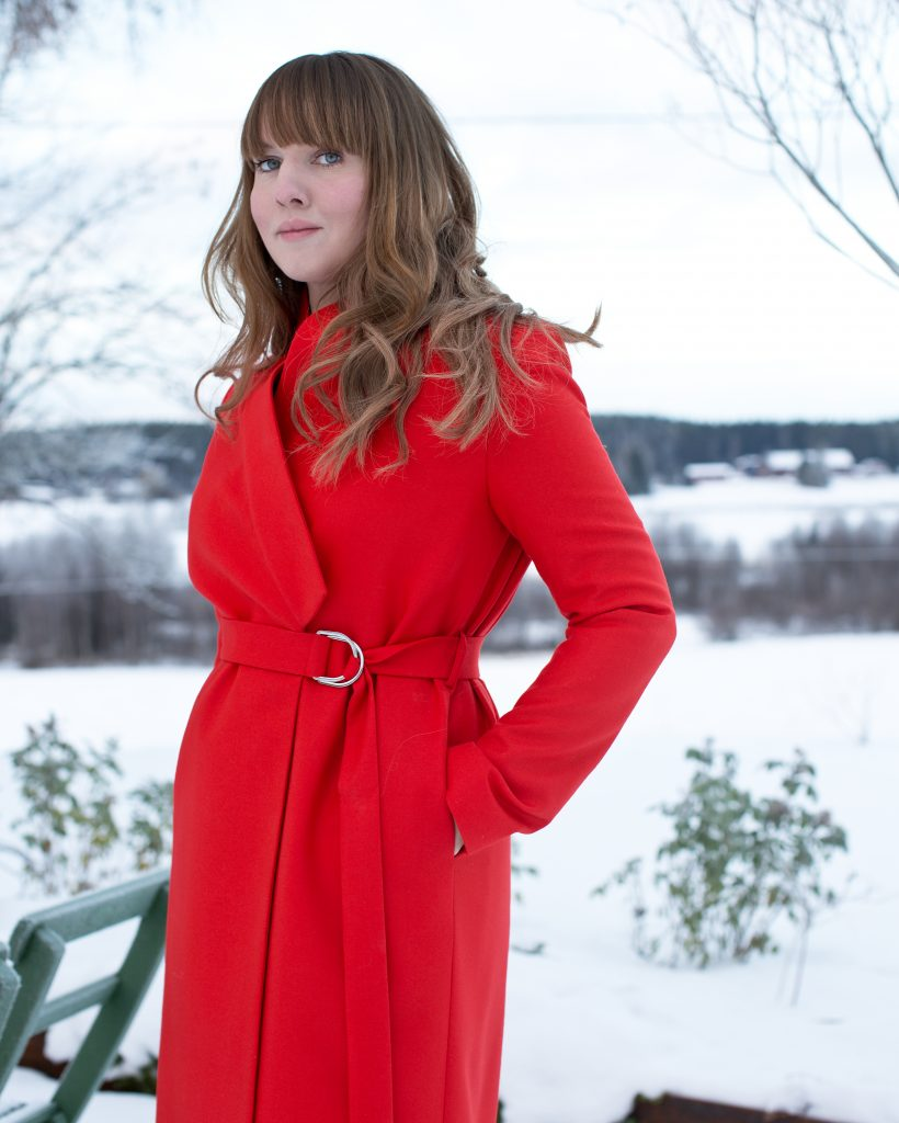 Clara i röd ullkappa med bälte i midjan.