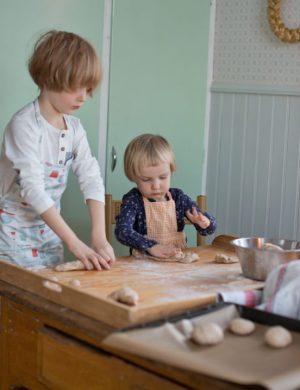 Bertil och Folke står vid bakbord i köket och rullar bröd.