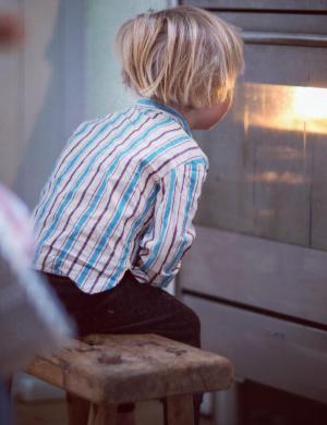Pojken Folke sitter på träpall framför spisluckan och väntar på bröd som ska gräddas.