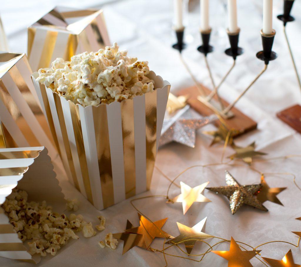 Festbord med popcorn i guldvita pappersbägare.
