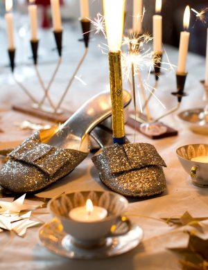 Festsko i silverglitter som en del av dukningen på ett nyårsbord.