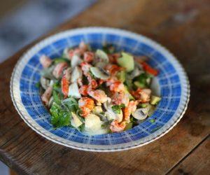 Sallad med skaldjur serverad i blå djuptallrik på gammalt träbord.