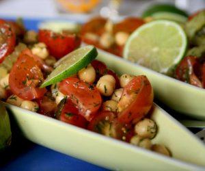Kikärtor och tomat blandade i avlånga små skålar. Serverade med lime.