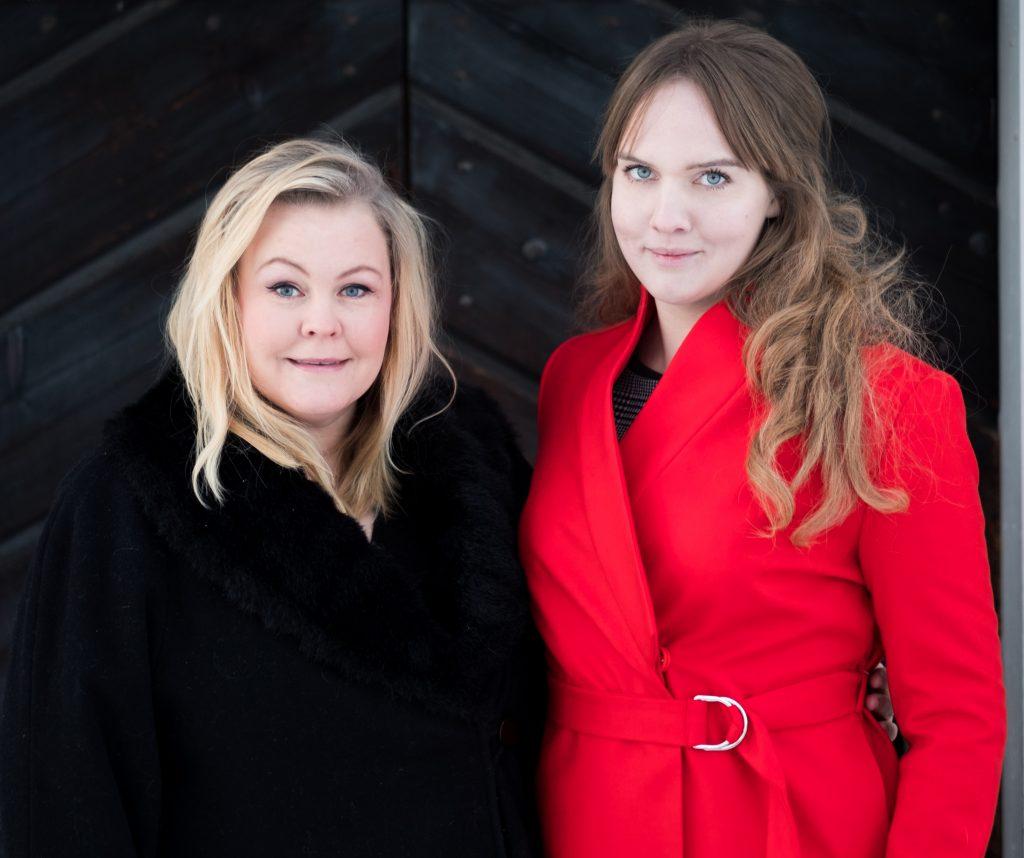 Clara med Erica Dahlgren utomhus i vinterväder. Står framför en mörk trädörr. Clara i röd kappa.