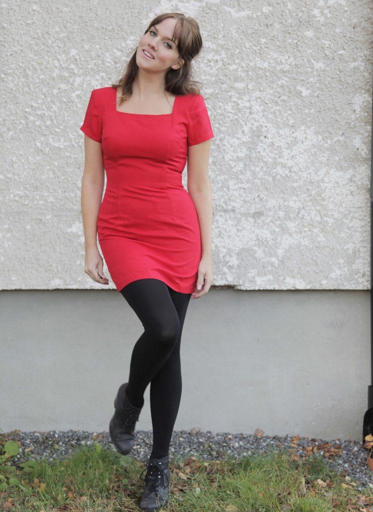 Clara i röd fodralklänning och svarta strumpbyxor mot ljus husfasad.