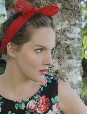 Clara utomhus i sommarväder och blommig klänning med scarf i håret, slänger ett ögonkast åt sidan.