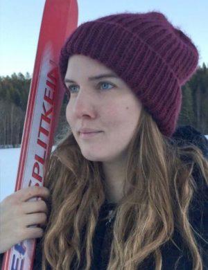 Clara med längdskidor i handen och mössa på huvudet utomhus vintertid.