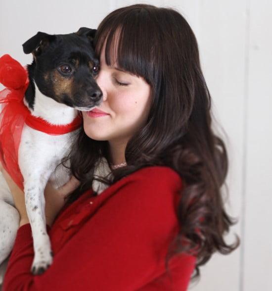 Clara i röd kofta gosar med hunden Melker som har en röd rosett om halsen.
