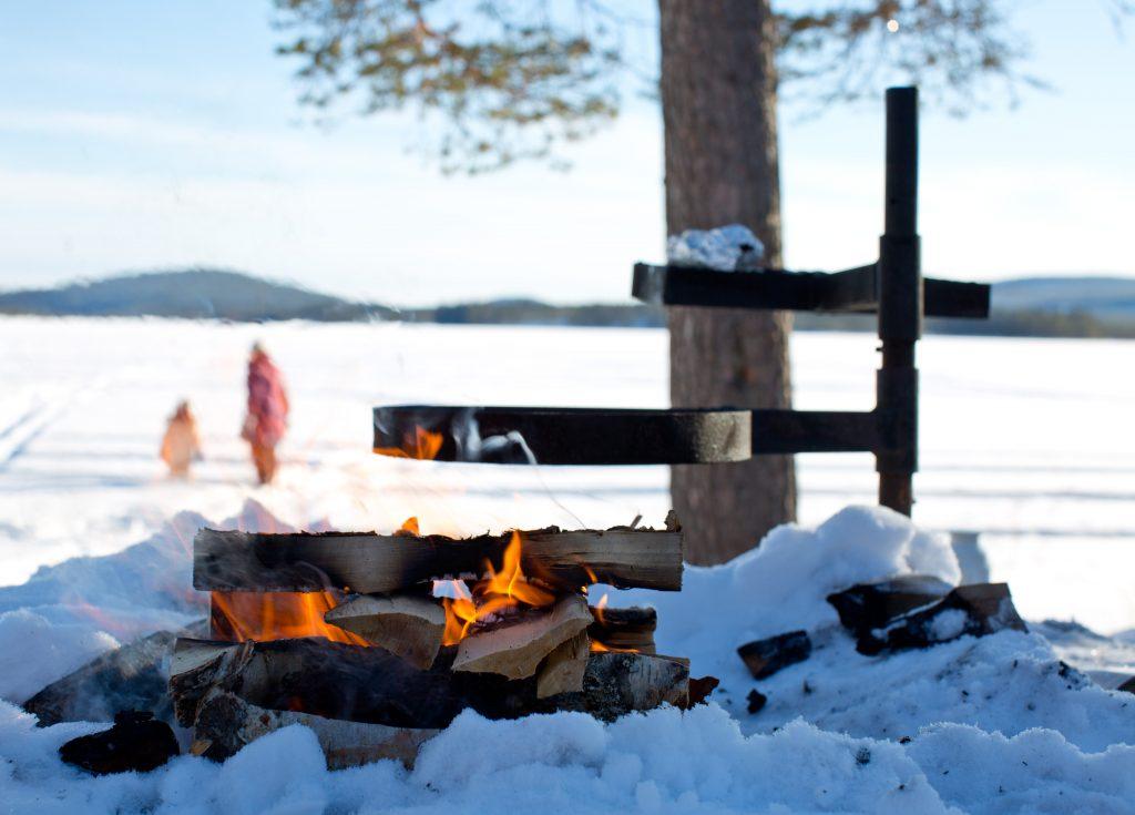 levande grilleld utomhus i snölandskap.