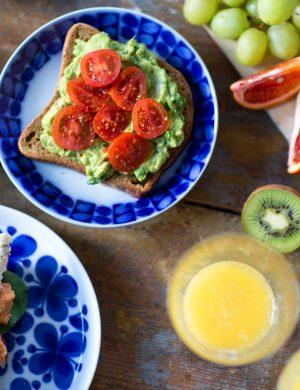 Bröd med glänsande grönsaker och avokadoröra på, fotat ovanifrån med juiceglas och skuren kiwi och annan frukt intill.