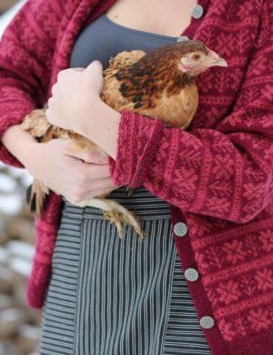 Clara i vårkläder och kofta håller en höna i famnen.