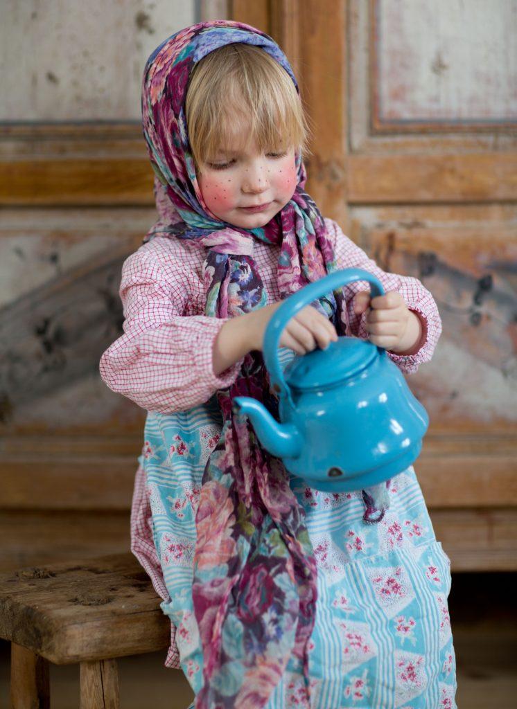 Folke utklädd till påskkärring med huckle, sitter och håller i en blå kaffepanna i emalj.