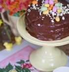 Mörk rund chokladtårta med färgglada godisägg på toppen.